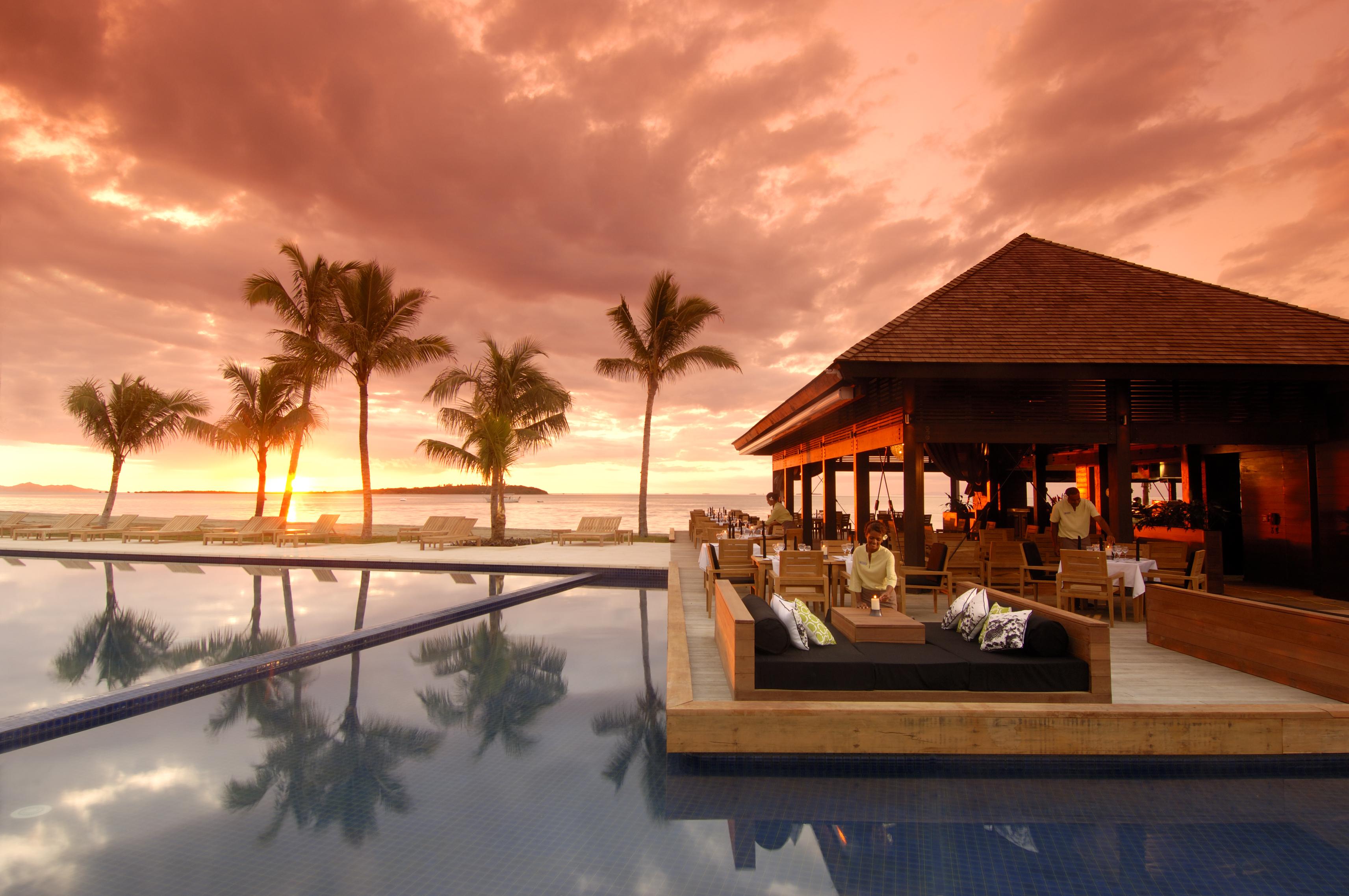 Un bellissimo tramonto su una baia con un ristorante interamente in legno