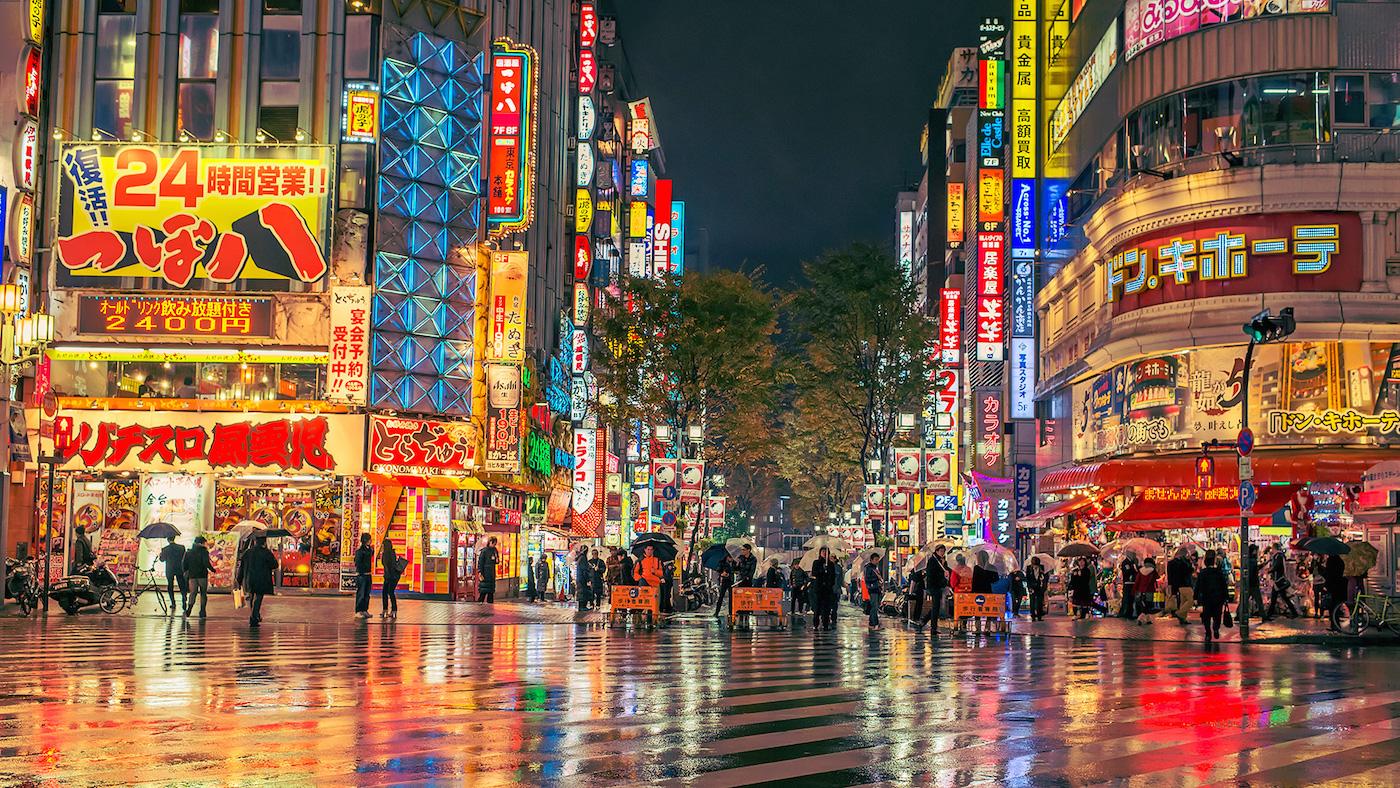 Un incrocio di una città giapponese di notte completamente illuminata di mille colori