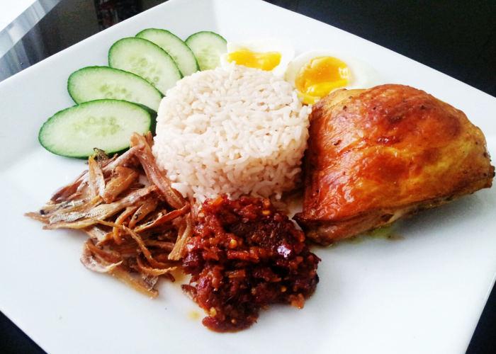 Il Nasi Lemak servito con pollo cetrioli uova e acciughe fritte