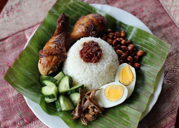 Il Nasi Lemak servito con pollo cetrioli uova acciughe fritte e arachidi tostate