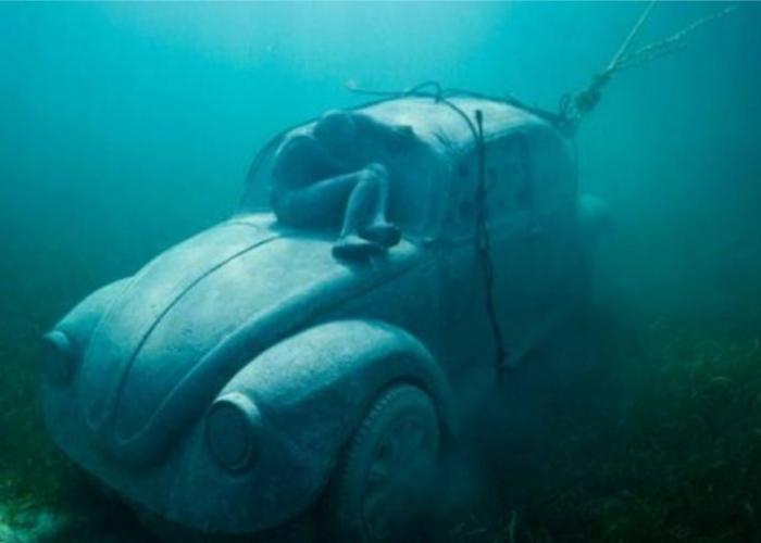 La statua di una automobile affondata con una persona che sembra dormirci sopra al MUSA